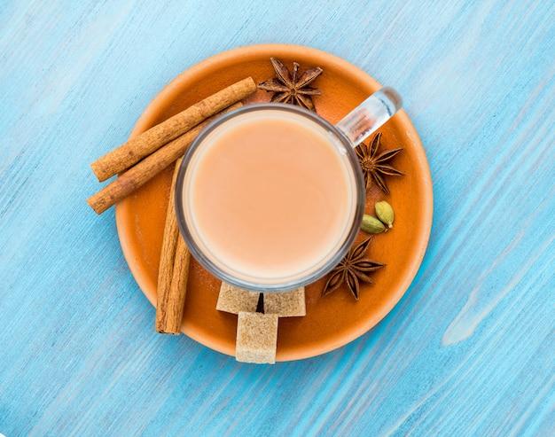 Masala bebida indiana no festival de holi. chá com leite e especiarias em uma caneca de vidro.