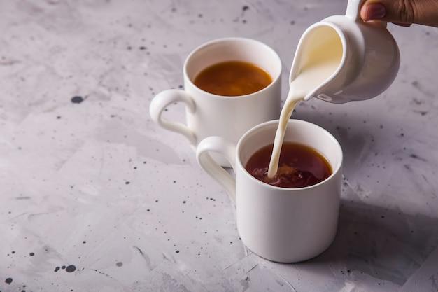Masala chá em xícaras minimalistas brancas sobre uma mesa cinza