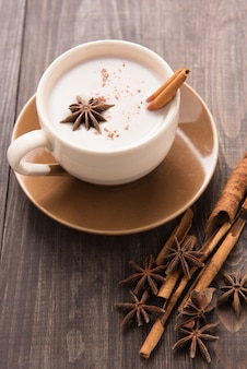 Masala chai com especiarias canela, cardamomo, gengibre, cravo e anis estrelado em fundo de madeira