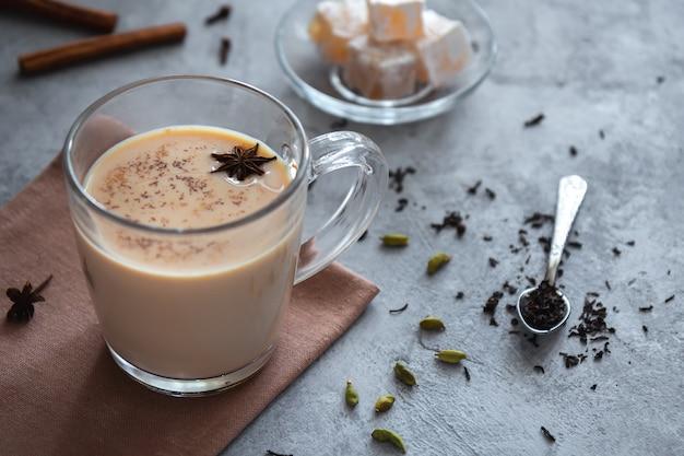 Masala chai com especiarias e leite em um copo transparente