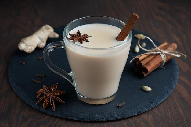 Masala chai indiano ou chá de especiarias misturado com erva-doce, canela e gengibre em copo de vidro na mesa de madeira