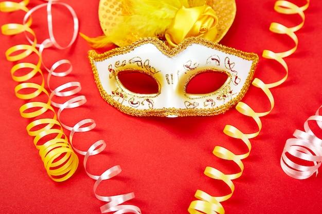 Máscara amarela e branca do carnaval no vermelho.
