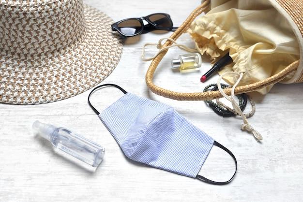 Máscara artesanal de tecido e desinfetante mão sobre uma mesa com acessórios de beleza e handbad