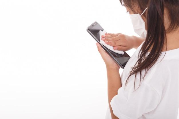Máscara asiática do desgaste da menina que limpa a tela do smartphone com álcool na parede branca.