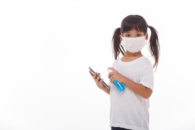 Máscara asiática do desgaste da menina que limpa a tela do smartphone com álcool
