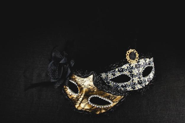 Máscara branca e dourada em um fundo escuro