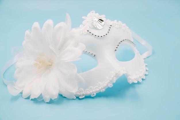 Máscara branca elegante com flor grande
