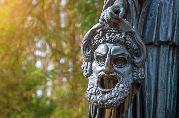 Máscara chorosa de uma escultura de cobre em um parque florestal