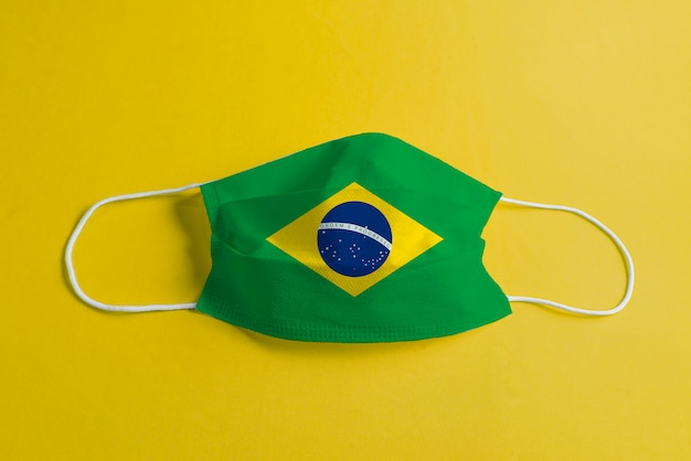 Máscara cirúrgica em fundo amarelo com bandeira do brasil