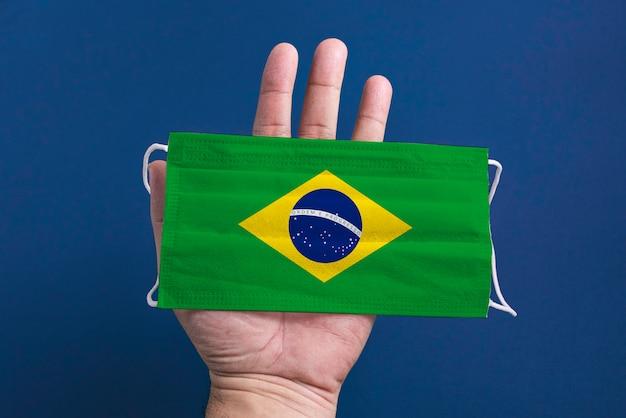 Máscara cirúrgica sobre fundo azul com bandeira do brasil - mão de homem segurando