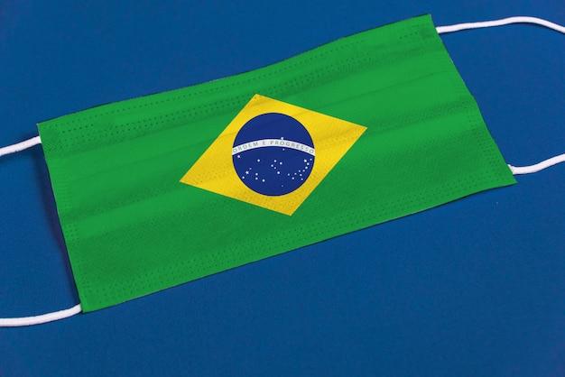 Máscara cirúrgica sobre fundo azul com bandeira do brasil