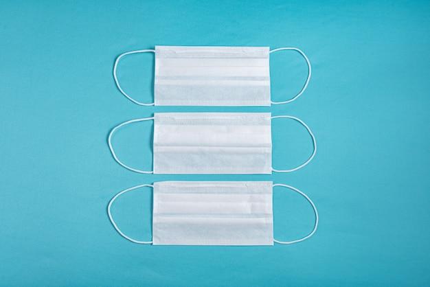 Máscara cirúrgica sobre fundo azul minimalista