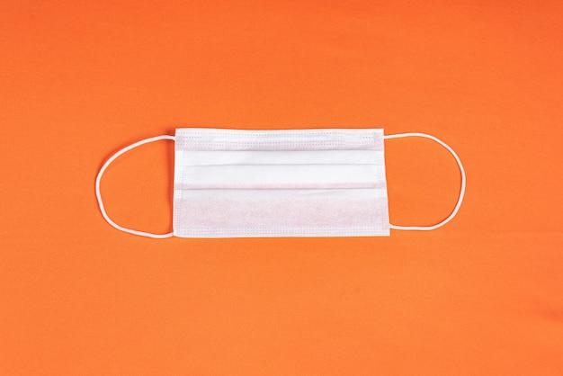 Máscara cirúrgica sobre fundo laranja minimalista