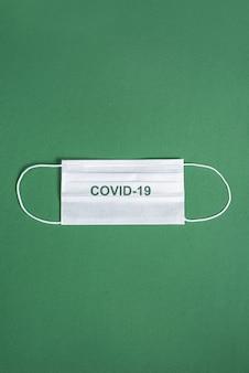 Máscara cirúrgica sobre fundo verde minimalista