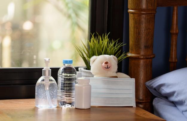 Máscara cirúrgica, ursinho de pelúcia e medicamento na mesa de madeira com natureza verde