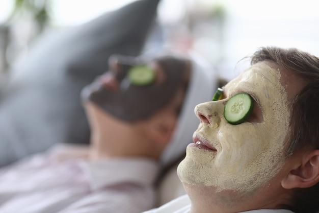Máscara cosmética foi aplicada nas faces masculina e feminina e fatias de pepino nos olhos.