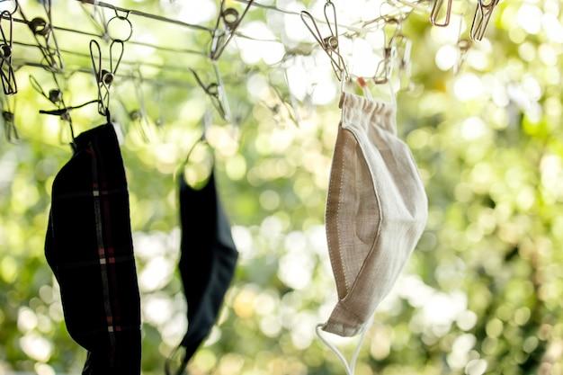 Máscara de algodão orgânico pendurado no varal. máscara lavável de tecido após a limpeza de lavagem para reutilização