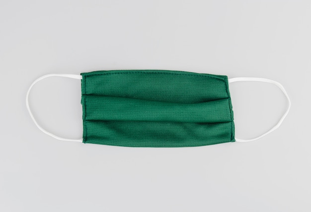 Máscara de algodão verde ou máscara de tecido em fundo cinza. poeira e vírus protetores. máscara preventiva de algodão para coronavírus. objeto em segundo plano. conceito de cuidados de saúde.