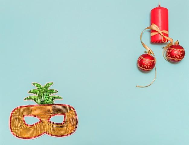 Máscara de ano novo em um fundo azul para o feriado e uma fita amarela no canto e uma vela. bolas vermelhas. decore com design.