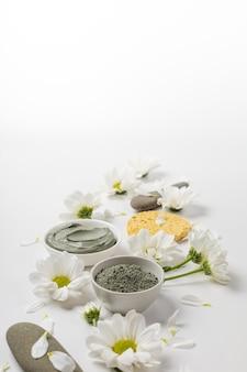 Máscara de argila natural seca e molhada com flores em um fundo branco