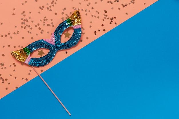 Máscara de baile de máscaras de carnaval e confetes com glitter dourados. vista superior, close-up sobre fundo azul e pêssego.