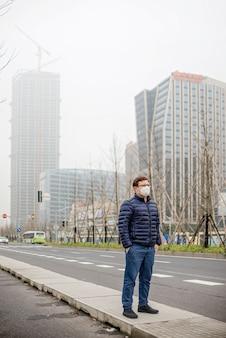 Máscara de boca vestindo do homem novo contra a poluição do ar ou o coronavírus. epidemia de pneumonia