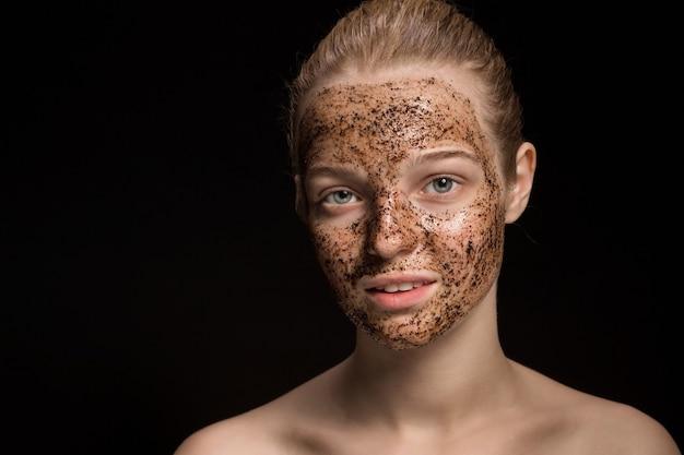Máscara de borra de café esfoliante para a pele no rosto de uma bela jovem