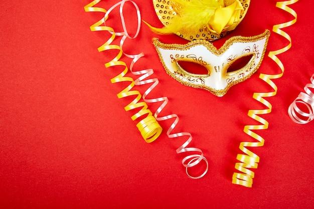 Máscara de carnaval amarelo e branco no vermelho.