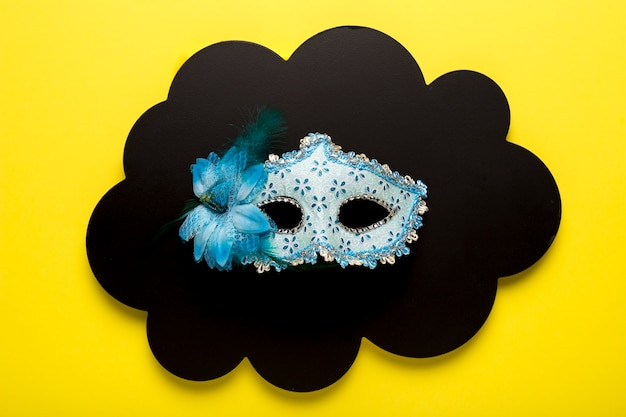 Máscara de carnaval azul na nuvem de papel preto