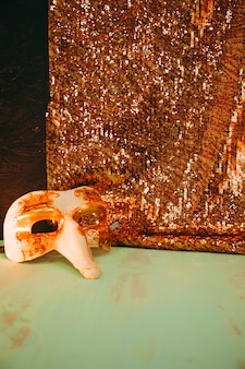 Máscara de carnaval branco perto da matéria têxtil de lantejoulas de brilho dourado na superfície resistida verde
