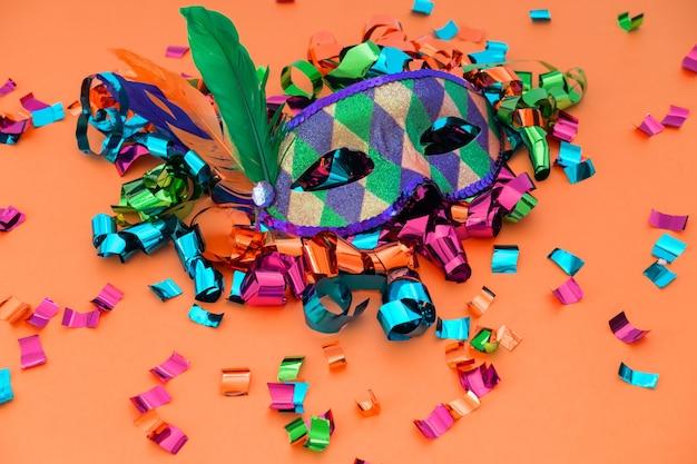 Máscara de carnaval colorida clássica com penas e confetes em fundo colorido.