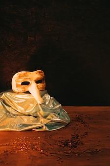 Máscara de carnaval de ouro vintage com lantejoulas escuras contra o pano de fundo