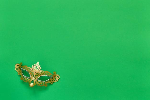 Máscara de carnaval dourada em verde. vista superior, copie o espaço.