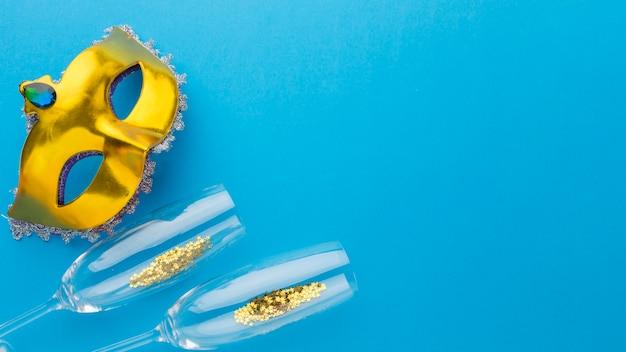 Máscara de carnaval dourado com copos de champanhe