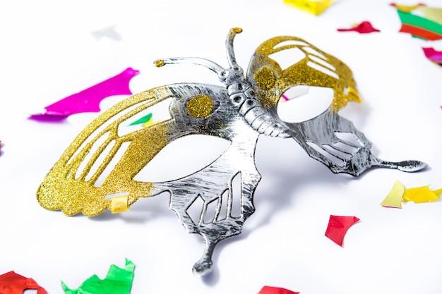 Máscara de carnaval e confetes coloridos.