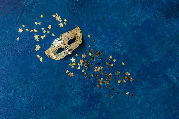 Máscara de carnaval e confetes glitter dourados
