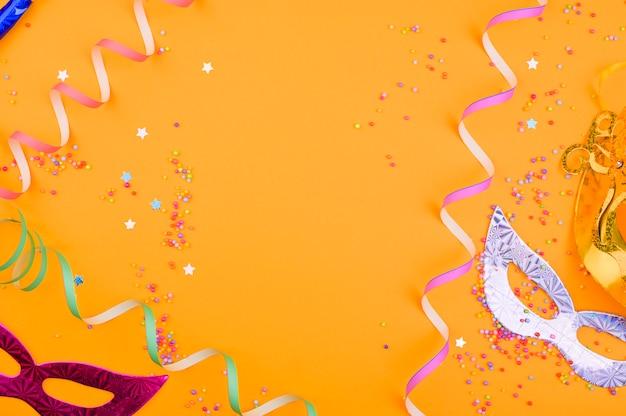 Máscara de carnaval e confetes sobre um fundo amarelo. decoração para um feriado tradicional italiano. copie o espaço. configuração plana
