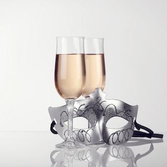 Máscara de carnaval e taças com champanhe no fundo branco