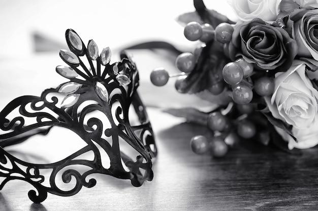 Máscara de carnaval em cima da mesa. o assunto da camuflagem em um encontro durante o carnaval. máscara veneziana em uma mesa de madeira em preto e branco.