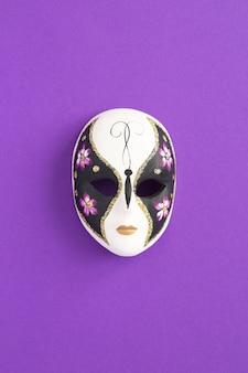 Máscara de carnaval veneziano no centro do fundo violeta. localização vertical. vista superior. copie o espaço.