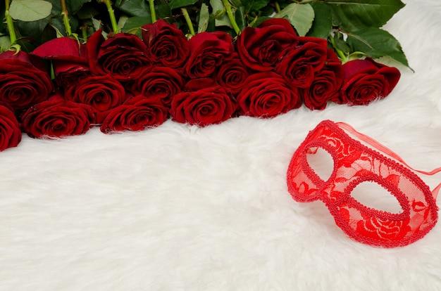 Máscara de carnaval vermelho encontra-se pêlo branco na superfície de um buquê de rosas