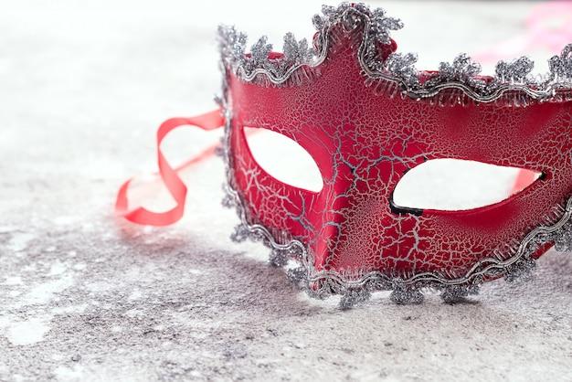 Máscara de carnaval vermelho lindo para o conceito de fundo de feriado de carnaval na pedra