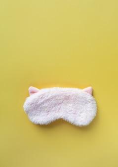 Máscara de dormir de pele fofa rosa pastel com orelhas pequenas sobre fundo de papel amarelo pastel. vista superior, plana leigos, copie o espaço. conceito de sonhos vívidos. acessórios para meninas e mulheres jovens
