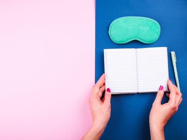 Máscara de dormir e página aberta do diário de sono