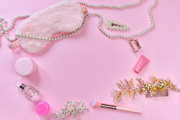 Máscara de dormir, produtos de higiene, acessórios femininos, perfumes, grampos de cabelo e itens femininos em uma superfície rosa