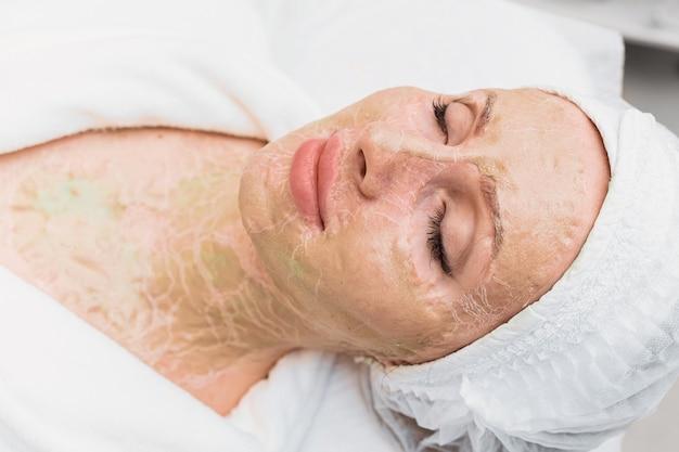 Máscara de enzima seca no rosto e pescoço de uma mulher. rejuvenescimento e lifting em uma clínica de cosmetologia