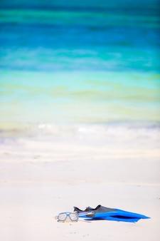Máscara de equipamento snorkling, snorkel e barbatanas na areia na praia branca