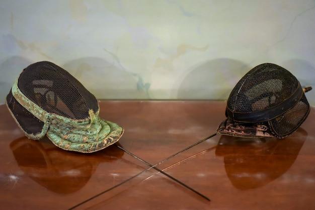 Máscara de esgrima velha em uma mesa em um liceu