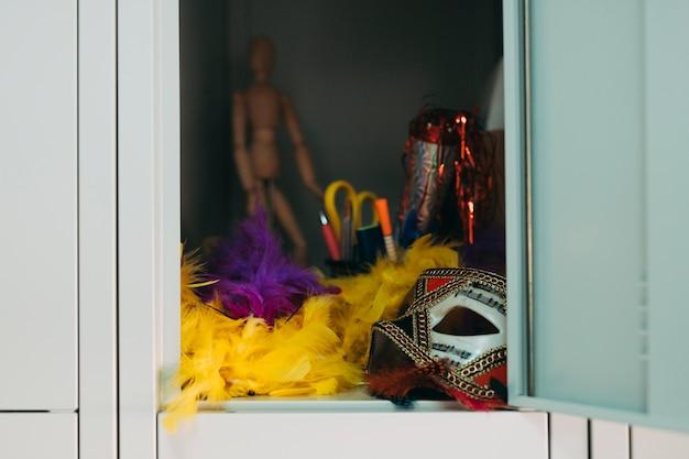 Máscara de festa; boa de pena amarela e roxa no cacifo