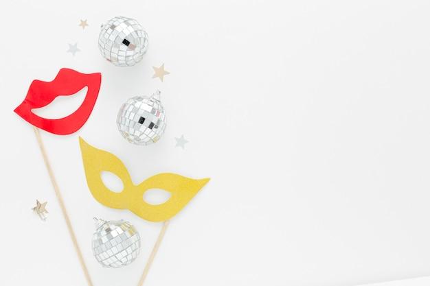 Máscara de festa com globos de prata na mesa